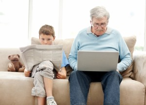 Man and child sitting on the sofa, reading. Both are slouched with heads going down