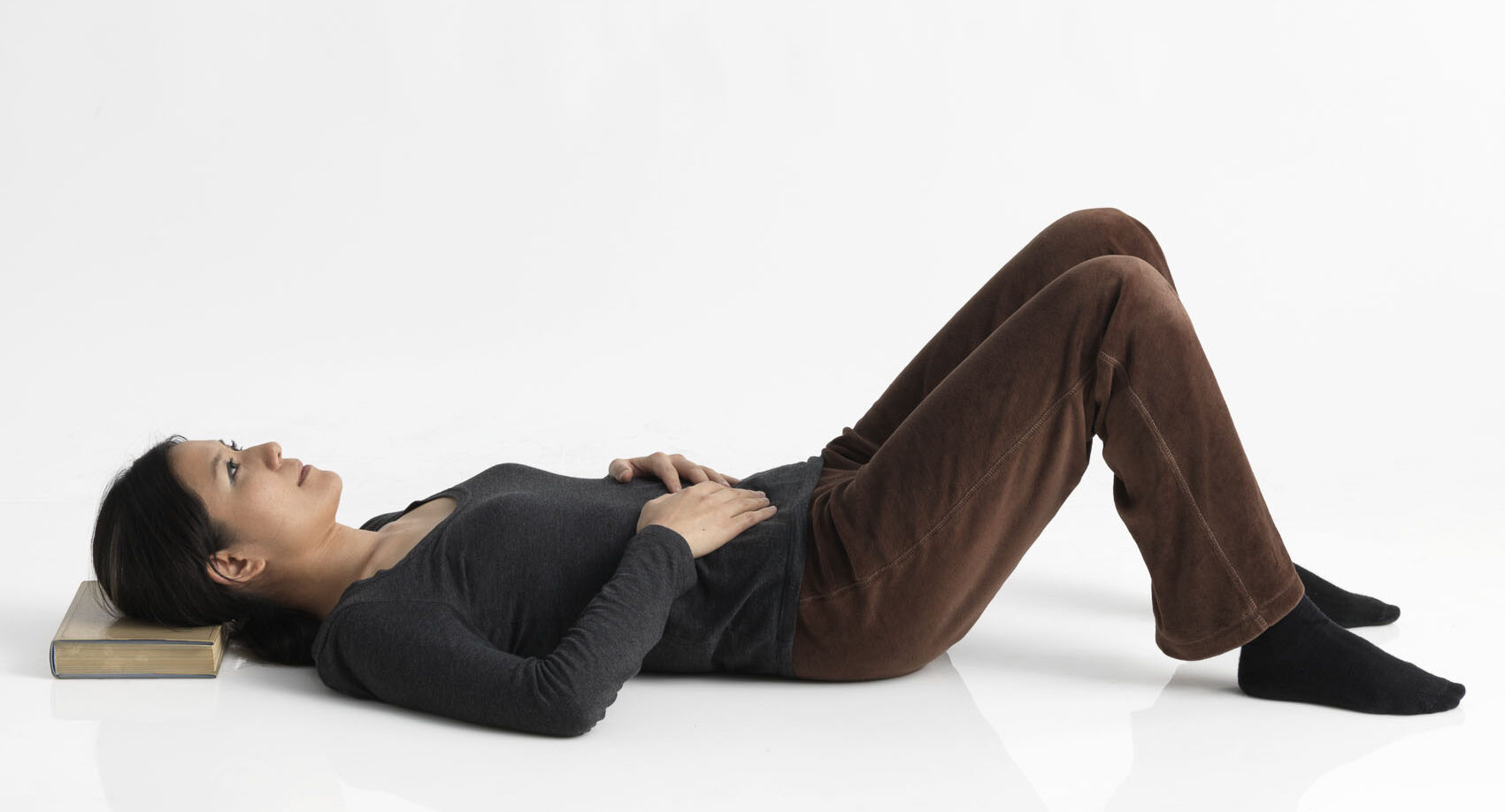 woman lying down on back, head on books, knees bent, feet on floor, hands on stomach