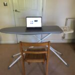 Working from home. Laptop open on an ironing board. Wooden chair in front of ironing board.