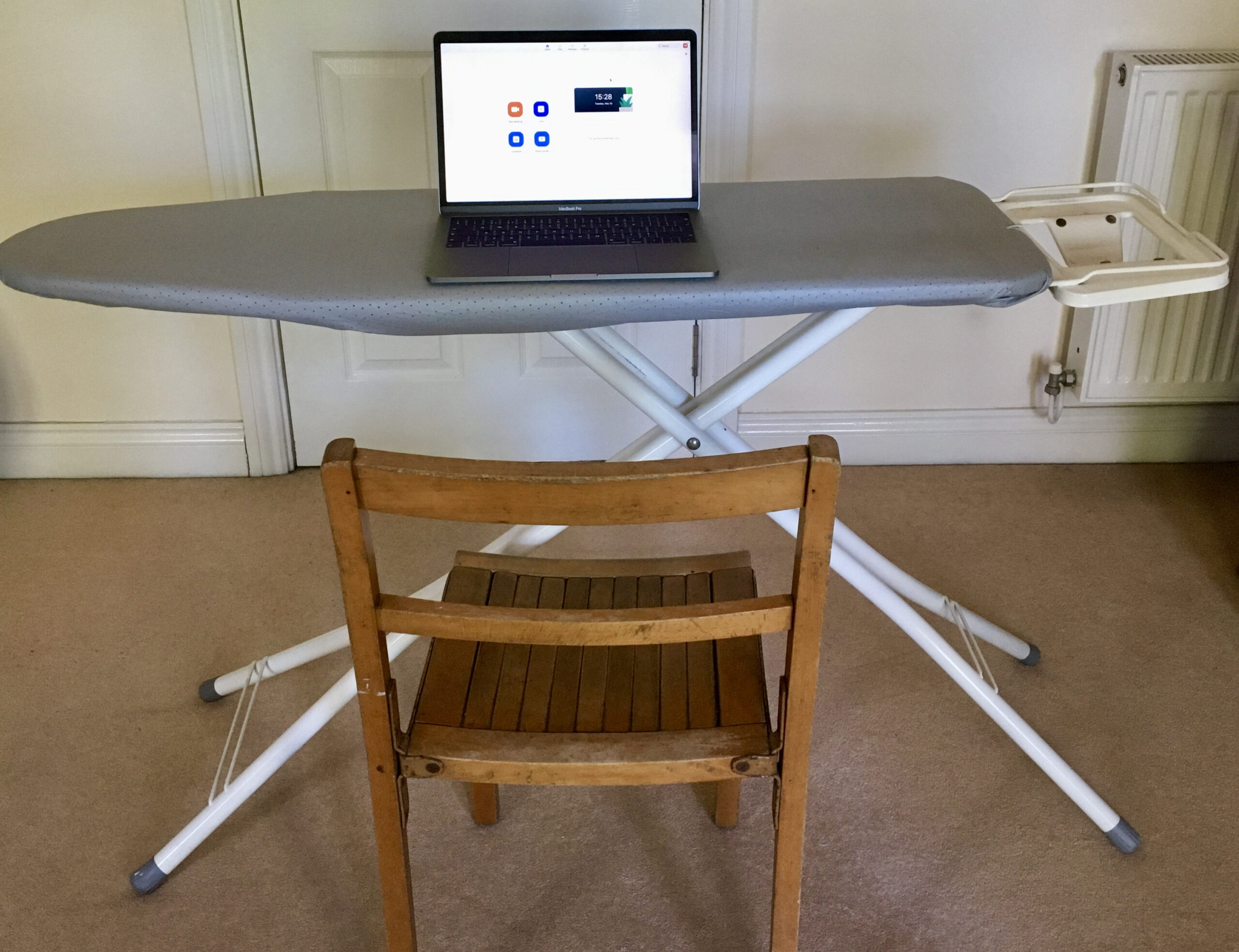 Working from home: a laptop opened on an ironing board with a chair in front. A sit stand desk!